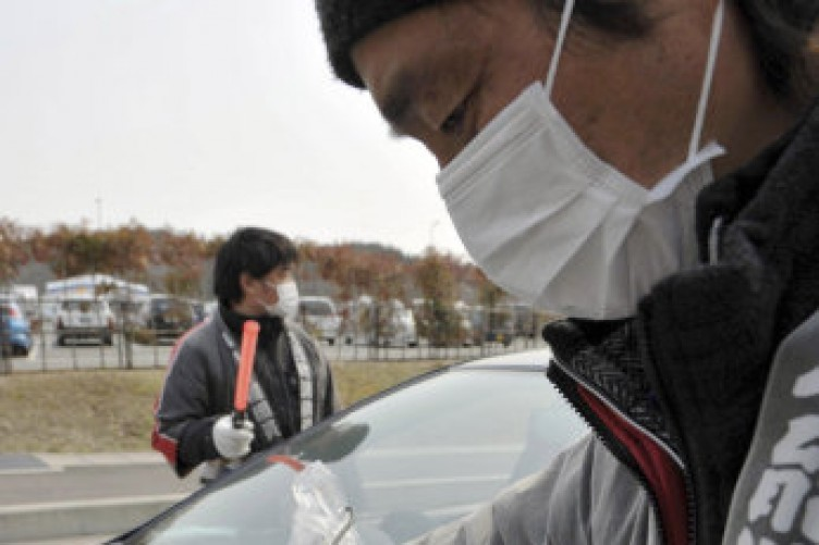 A fireman checks a devise to check the level of radiation on a vehicle before its owner and resident evacuates to other city, in Tamura city, Fukushima prefecture, northeastern Japan, Saturday, April 2, 2011.
