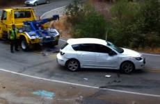 Tow truck driver watches helplessly as car rolls downhill