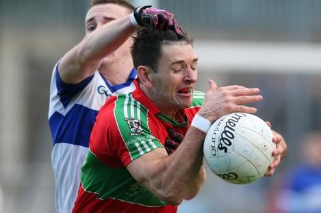Ballymun's Derek Byrne tackled by Jarlath Curley of St Vincent's.