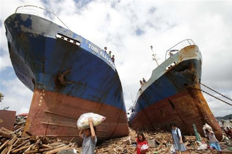 Survivors pass by two large boats after they were washed ashore by strong waves caused by Typhoon Haiyan in Tacloban city, Leyte province central Philippines