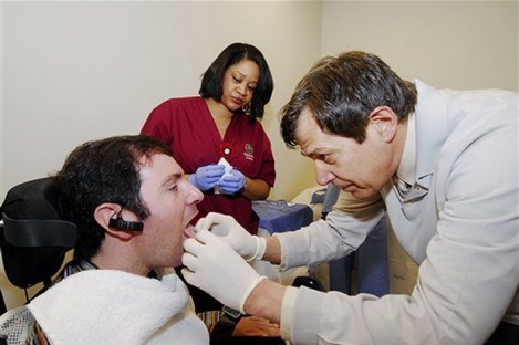 Jason DiSanto, left, receiving a tongue piercing at Georgia Tech in Atlanta. An experimental device is letting paralyzed people drive wheelchairs simply by flicking their tongue in the right direction.