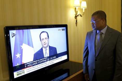 Prime Minister of the Central African Republic Nicolas Tiangaye watches French President Francois Hollande on TV
