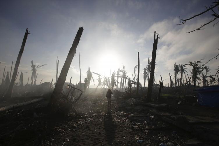 A typhoon survivor walks past damaged trees at typhoon-ravaged Tolosa town, Leyte province, central Philippines on Monday.