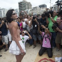 Topless rights protest attracts just four women... and over 100 photographers
