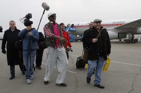 Rodman arriving at Pyongyang airport with his entourage, including Cooper (far left), earlier today.