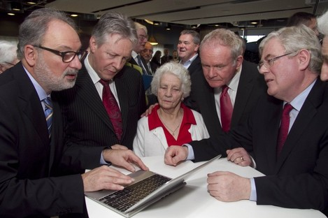 Piet Chielens, First Minister of Northern Ireland Peter Robinson, Deputy First Minister Martin McGuinness and Tánaiste Eamon Gilmore show the database to a woman who had relatives fighting in World War I.