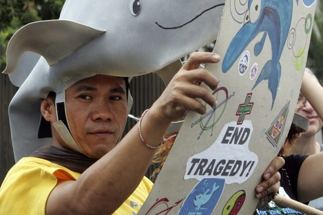 An animal rights advocate, wearing a dolphin hat, displays a placard during a picket at the Japanese Embassy in Manila, Philippines