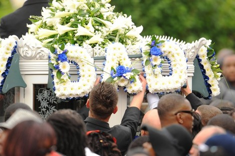 Mourners place flowers on a horse-drawn carriage following the funeral of police shooting victim Mark Duggan at the New Testament Church of God in Wood Green, north London, on 9 September 2011.