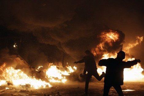 Protesters throw stones during clashes with police in central Kiev, Ukraine yesterday.