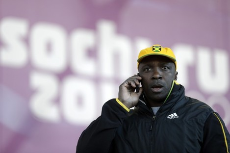 Winston Watts, the driver for JAM-1 of Jamaica, speaks on the phone after arriving at the sliding center during a training session for the men's two-man bobsled at the 2014 Winter Olympics