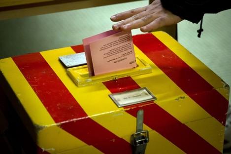 A voter puts his ballot into a box at a polling statio near Geneva today.