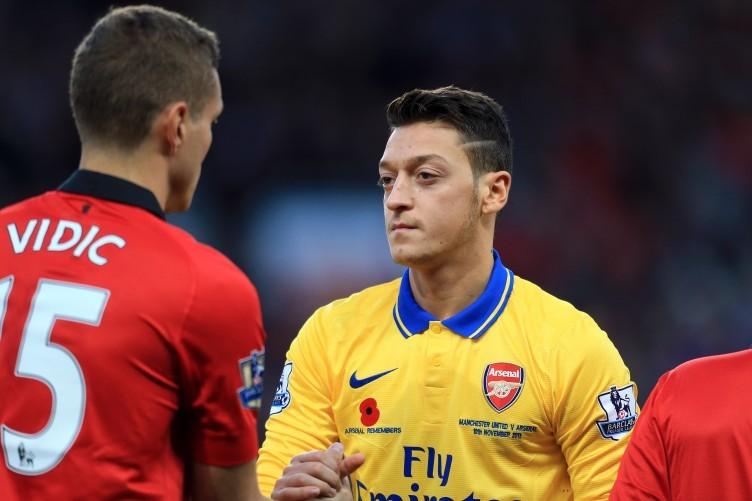 Manchester Untied captain Nemanja Vidic and Arsenal's Mesut Ozil.