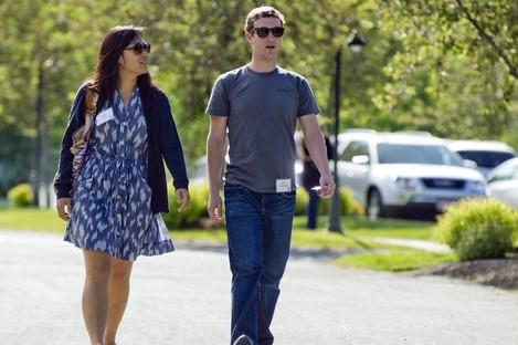 Mark Zuckerberg, president and CEO of Facebook, walks with Priscilla Chan