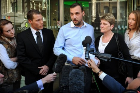 Paul King (centre), the son of Ian Tomlinson, and his widow Julia (2nd right) speak to the press after the inquest into Mr Tomlinson's death was delivered as an unlawful killing.