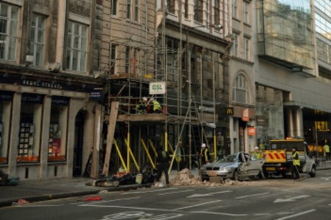 Workmen clear debris at the scene in Kingsway, opposite Holborn Tube station in central London, after a woman, named by police as Julie Sillitoe, 49, was killed when large chunks of masonry fell from the building above the Hiba restaurant on to her car.