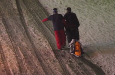 Two guys helping their drunk friend get home in a ski resort