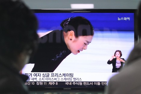 People watch a TV news showing Yuna Kim of South Korea at the women's free skate figure skating final during the 2014 Winter Olympics.