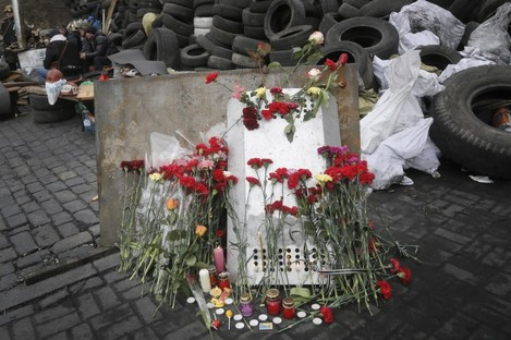 Flowers cover a protester's shield on the site where he was killed by a riot police sniper during a recent deadly clash close to Kiev's Independence Square.