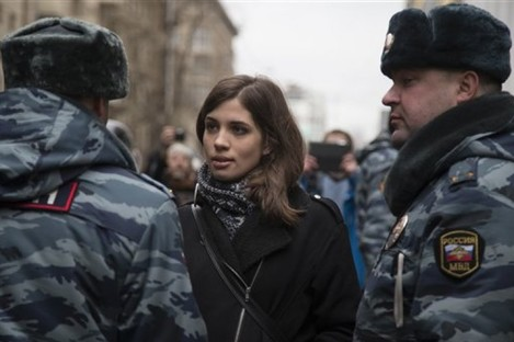 Member of the Pussy Riot punk group, Nadezhda Tolokonnikova, center, speaks to a police officer outside Zamoskvoretsky District Court in Moscow, Russia.