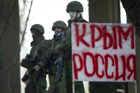 Unidentified gunmen wearing camouflage uniforms block the entrance of the Crimean Parliament building in Simferopol, Ukraine