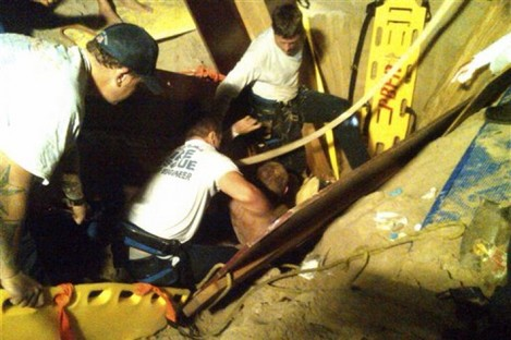 Maly is pulled from his sandy tomb by rescuers in Florida