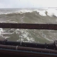 Huge wave smashes through restaurant window as people eat breakfast