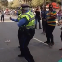Older policeman joins street party with booty-shaking dance