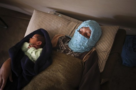 Syrian refugee Um Raad, 30, from Daraa, holds her 6 day-old son, Abdullah, at the Moroccan field hospital in Zaatari refugee camp near the Syrian border, in Mafraq, Jordan.
