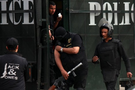 Riot police are seen getting ready at a police van outside a Cairo university.