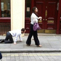 A businessman is being walked around London on a lead