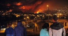 Sixteen people have died in a huge fire consuming the outskirts of a Chilean port city