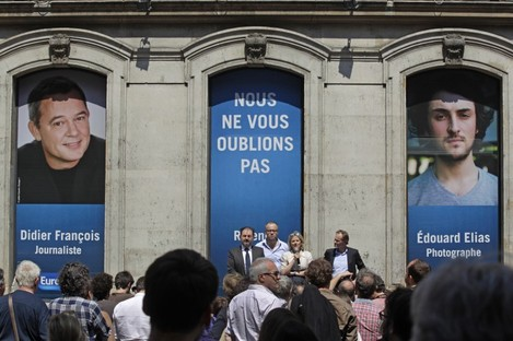 Florence Aubenas, holding a microphone at center, a French journalist who was held hostage in Iraq, delivers her speech during a gathering for Europe-1 radio reporter Didier Francois and independent photographer Edouard Elias.