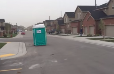 Runaway portaloble toilet makes a break for it down windy street