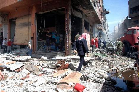 Syrian people gather at the site of one of two car bombs that exploded in the pro-government district of Zahra in Homs