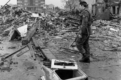 A soldier stands guard over the shattered remains of McGurk's bar in North Queen Street, Belfast.