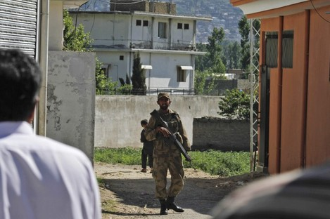 A Pakistan army soldier secures a street in front of the house in which Osama bin Laden was killed (background).