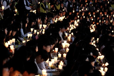 High school students hold candles during a rally to pay tribute to the victims and missing passengers of the sunken ferry Sewol in Ansan.