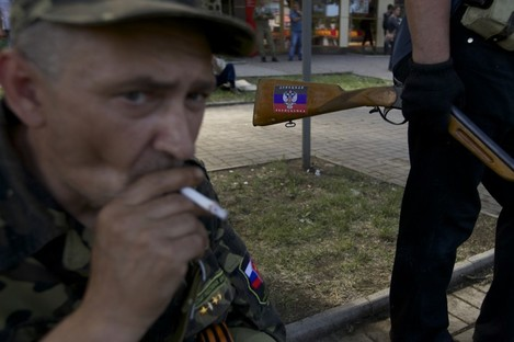 A sticker with Donetsk people's republic colors is seen on the hunting rifle of a local man who came to a check point on a road leading to the airport, in Donetsk