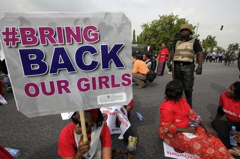 A police officer stands guard as people attend a demonstration calling on the government to rescue the kidnapped girls.