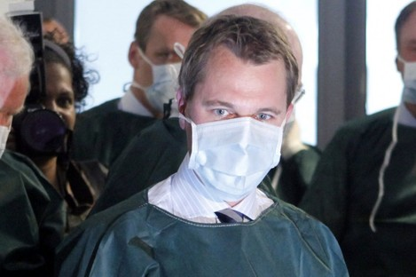 German Health Minister Daniel Bahr wears protective clothes during a visit to a German hospital on Sunday.