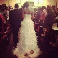 Bride walks down aisle with newborn baby attached to her dress