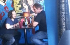 Just Quentin Tarantino having lunch under a Pulp Fiction poster