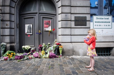 A girl stands next to flowers at the Jewish Museum in Brussels after three people were killed in a shooting.