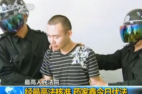 This TV grab shows two masked officers taking Yao Jiaxin to the execution field in Xian city, northwest Chinas Shaanxi province, 7 June 2011.