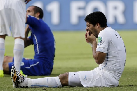 Luis Suarez holds his teeth after clashing with Giogio Chiellini of Italy.