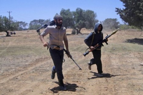 Rebel fighters run during heavy fighting with pro-Gadhafi forces on the frontline of Dafniya 40 km west Misrata, Libya, Sunday, June 12, 2011.