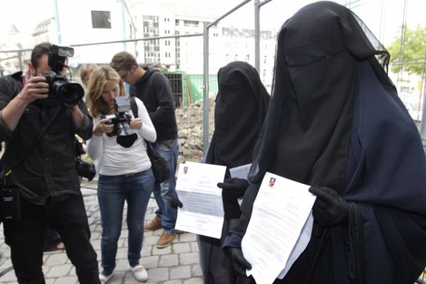 Two sisters who were fined each €50, after they were caught wearing the full veil in public, show their citations to media outside the town hall in Brussels in August 2011.