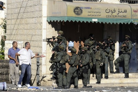 A Palestinian man argues with Israeli border police in Jerusalem yesterday.