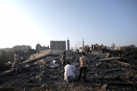 Palestinians search in the rubble of a house destroyed by an overnight Israeli airstrike in Gaza City