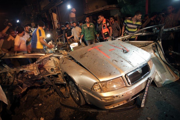 Palestinians search the wreckage of vehicle reportedly belonging to a taxi driver working for a local media company following an Israeli air strike in Gaza City.